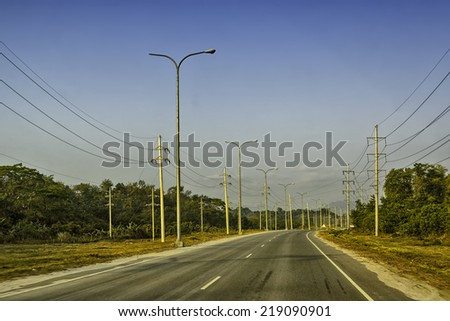 Sunrise over a newly built concrete road, Philippines - stock photo