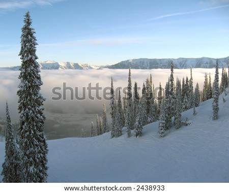 Sunrise over a snowy, cloudy valley - stock photo