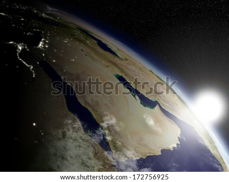 Sunrise over Arabian peninsula viewed from space. Highly detailed planet surface with clouds and city lights. Elements of this image furnished by NASA. - stock photo