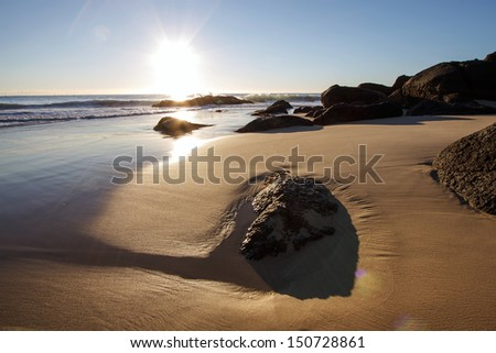 Sunrise over beach with rocks in foreground - stock photo