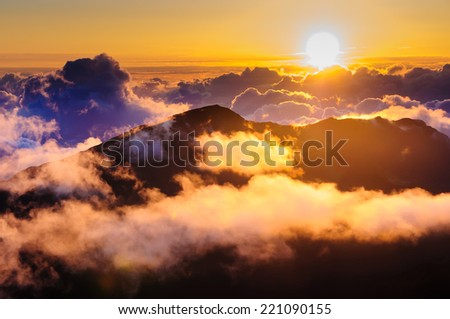 Sunrise over clouds and distant mountains from on top of Haleakala Crater, Maui, Hawaii, USA - stock photo