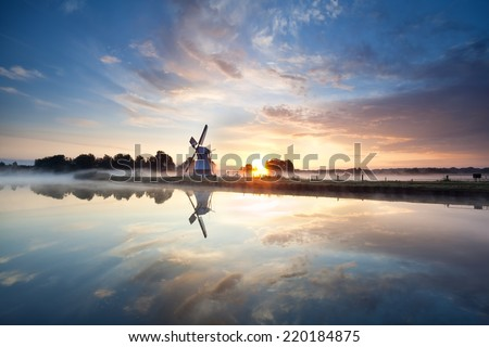 sunrise over Dutch windmill and river, Holland - stock photo
