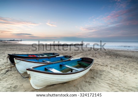 Sunrise over fishing boats on Bournemouth Beach - stock photo