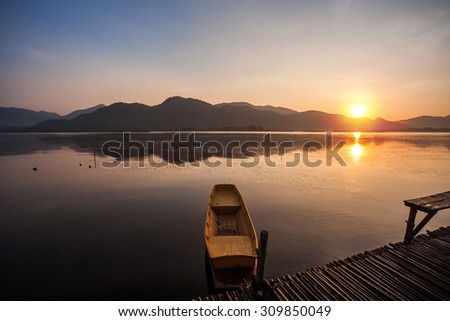 Sunrise over lake and mountain - stock photo