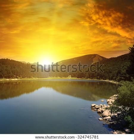 sunrise over lake and mountains - stock photo