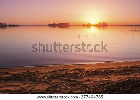 Sunrise over lake in early spring - stock photo