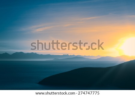 Sunrise over Lake Titicaca and the mountains of the Andes viewed from the popular tourist destination of Isla del Sol (Island of the Sun) in Lake Titicaca, Bolivia - stock photo