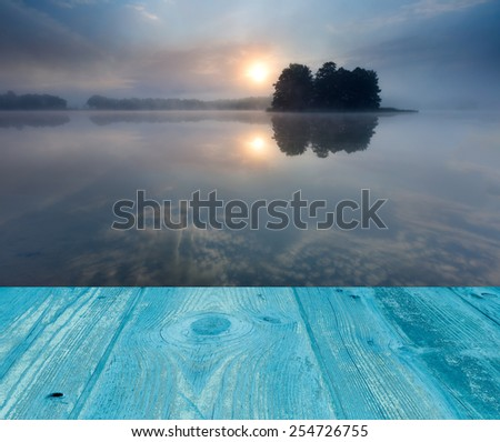 sunrise over lake with wooden floor on foreground - stock photo