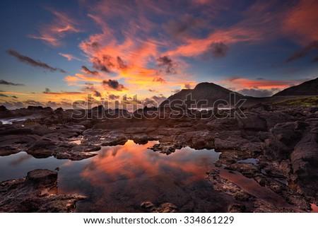 sunrise over Makapu'u point and lighthouse from Makapu'u beach, Oahu, Hawaii, USA - stock photo