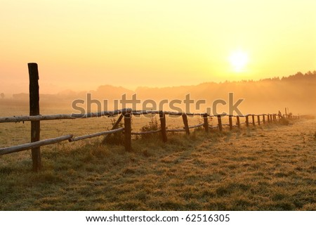 Sunrise over misty grassland with wooden fence in the foreground. Photo taken in October. - stock photo
