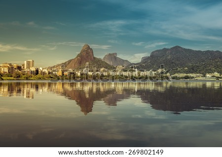 Sunrise over mountains in Rio de Janeiro with water reflection and light leak, Brazil - stock photo