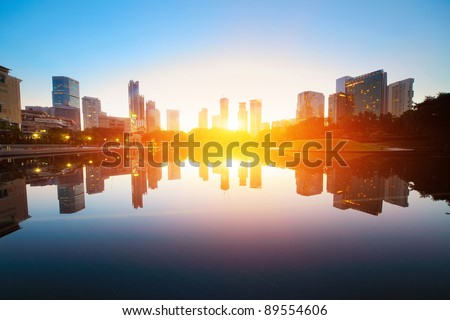 Sunrise over pond in a city. Kuala Lumpur skyline - stock photo