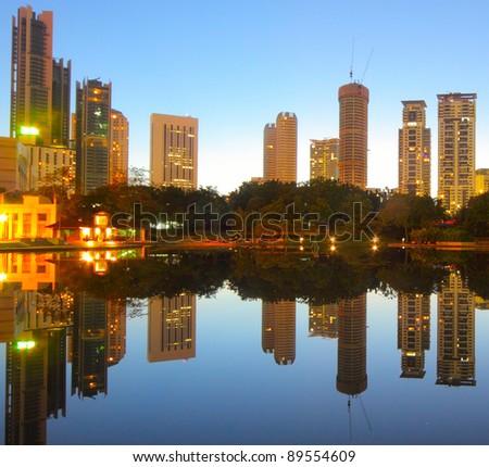 Sunrise over pond in a city. Kuala Lumpur skyline - stock photo