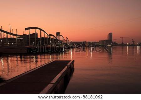 Sunrise over Port Vell , with silhouette of Rambla del Mar, the Marina and waterfront buildings - stock photo