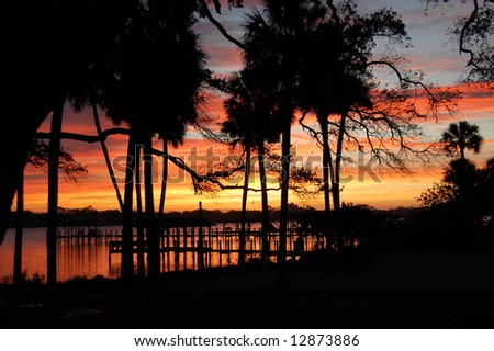 Sunrise over river docks - stock photo