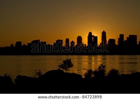 Sunrise over Seattle Washington Skyline Along Puget Sound from Alki Beach - stock photo