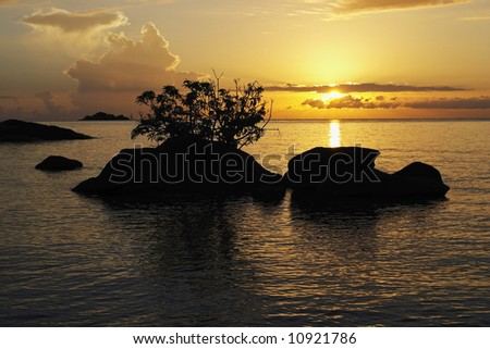 Sunrise over sihouetted rocks, Makuzi Beach, Malawi. The rising sun is reflected in the tranquil rippled waters of Lake Malawi. Salmon pink and orange clouds fill the sky. - stock photo