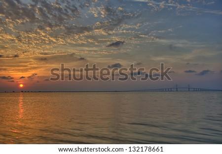 Sunrise over Tampa Bay and the Sunshine Skyway Bridge - stock photo
