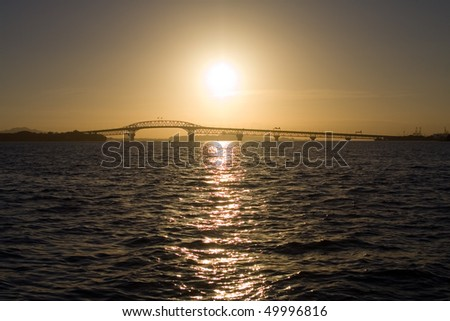 Sunrise over the Auckland Harbor Bridge and Waitemata Harbor - stock photo
