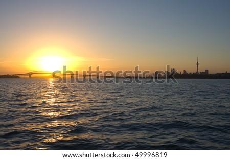 Sunrise over the Auckland Harbor Bridge, Auckland City and Waitemata Harbor - stock photo