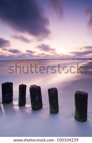 Sunrise over the Baltic sea, Poland. Photograph of breakwater in warm light of sun.