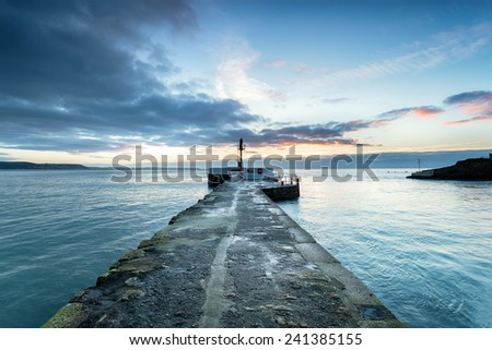 Sunrise over the Banjo Pier on the beach at Looe on the south Cornwall coast - stock photo