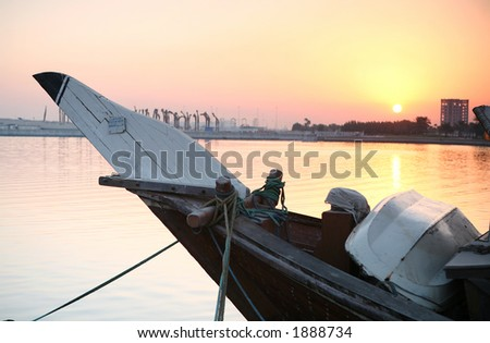 Sunrise over the bows of a Dhow in Doha, Qatar. The registration number of the boat has been removed making it generic - stock photo