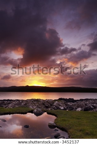 Sunrise over the calm waters of Loch Sligachan on the Isle of Skye, Scotland. Scattered clouds are tinged with orange, mauve and purple color - stock photo