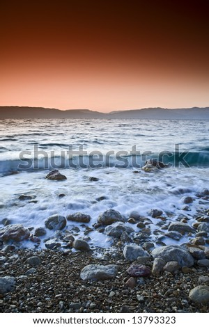 sunrise over the dead sea with waves in motion blur - stock photo