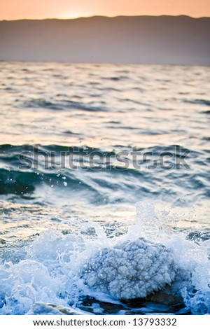 sunrise over the dead sea with waves splash over salt formation - stock photo