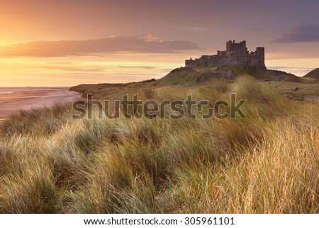 Sunrise over the dunes at Bamburgh Castle in Northumberland, England. - stock photo