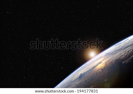 Sunrise over the Earth from space with stars in the background.  Elements of this image furnished by NASA.  - stock photo