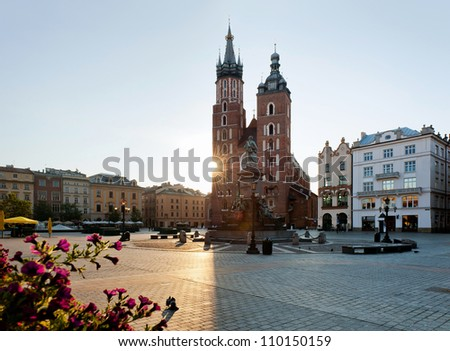 Sunrise over the market square in Krakow.Beautiful old part of Krakow city photographedi n warm  light of sunrise. - stock photo