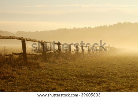 Sunrise over the misty field with a wooden fence in the foreground. - stock photo