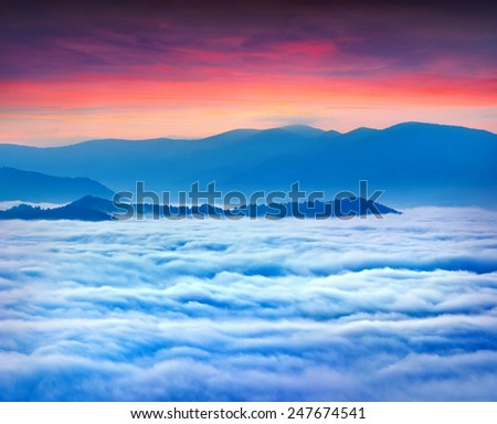 Sunrise over the sea of fog in the mountains at the summer. Dramatic sunset - stock photo