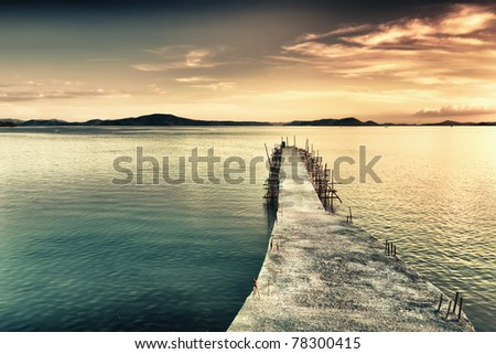 Sunrise over the sea. Pier on the foreground - stock photo