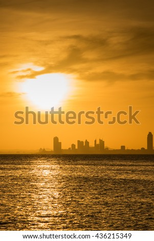 Sunrise over the sea with city background
