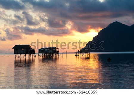 Sunrise over wooden homes on stilts by the island of Maiga, Sabah, Borneo. - stock photo