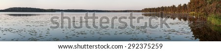 Sunrise panoramic view of coniferous forest big lake with coastline - stock photo