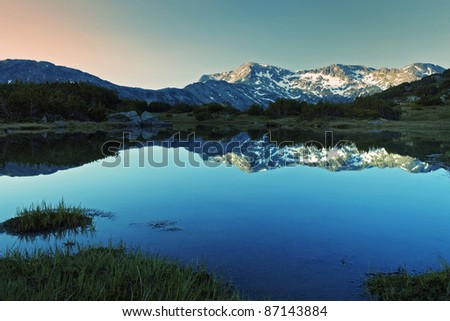 sunrise reflection on the mountain peak with snow - stock photo