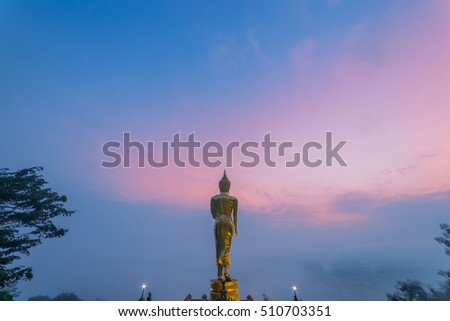 Sunrise scence of Golden Buddha statue standing on a mountain with sky and clouds at Wat Phra That Khao Noi, Nan Province, Thailand