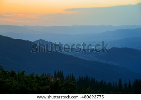Sunrise scene with mountain silhouette. Green trees in foreground.