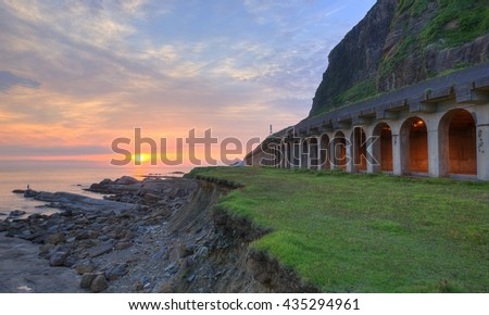 Sunrise scenery at a rocky beach with a coastal highway along the beautiful coastline under dramatic dawning sky ~ Scenic view of a rock shed tunnel at dawn on northern coast of Taipei, Taiwan - stock photo