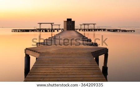 Sunrise shot taken early morning at Mar Menor, Murcia Spain in late summer. Long Exposure dawn photograph of a zig zag wooden jetty or pier reaching out to sea across the still water. - stock photo