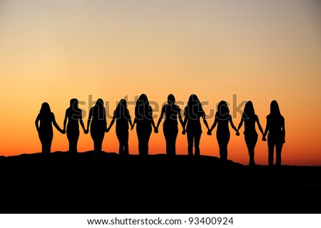 Sunrise silhouette of 10 young women walking hand in hand. - stock photo