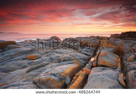 Sunrise skies rich red clouds paint the sky as the distinctive orange grey rocks contrast the scenic landscape.