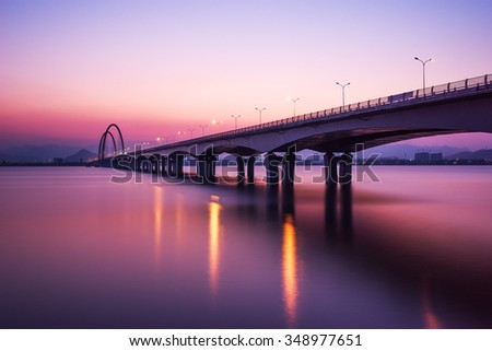 sunrise skyline and reflection of bridge over river