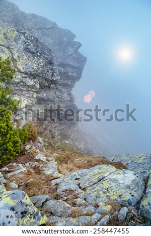 Sunrise / sunset view near stones in the mountains. Sunbeams that are breaking through the clouds. - stock photo