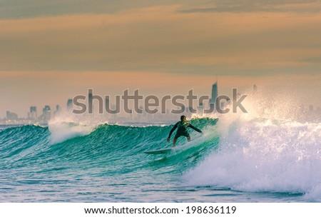 Sunrise Surf with Surfers Paradise on the Background - stock photo