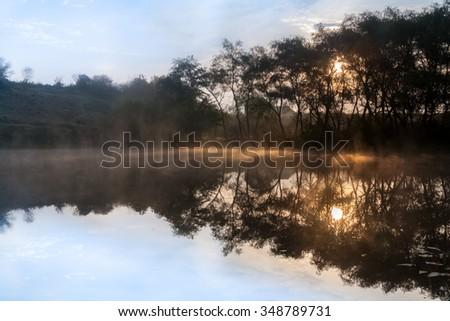 Sunrise, the morning mist over the lake. - stock photo